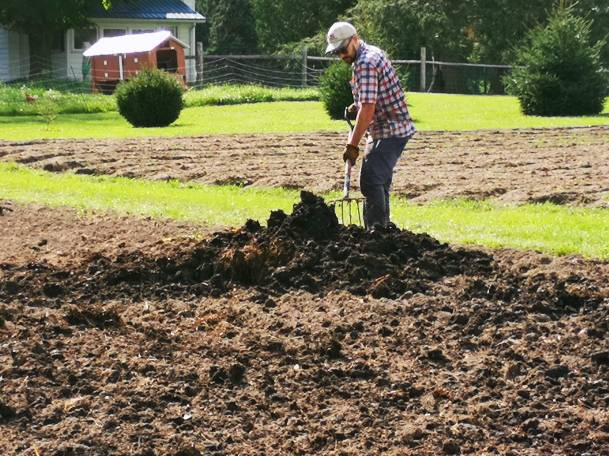 Jesse manually applies composted manure to the field block before seeding cover crops.